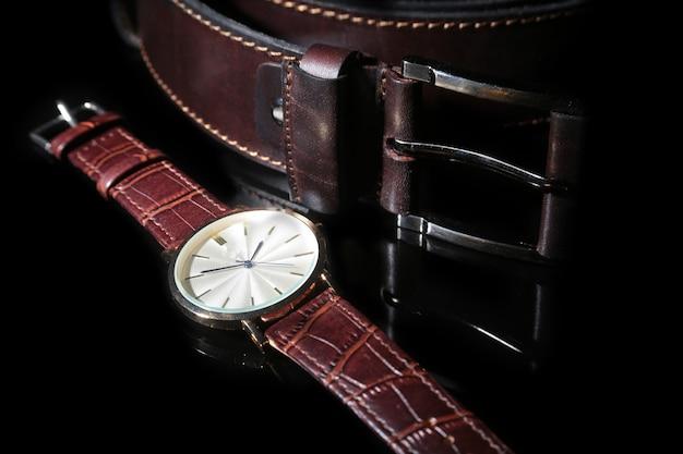 Herenaccessoires met bruine lederen portemonnee, riem en horloge.