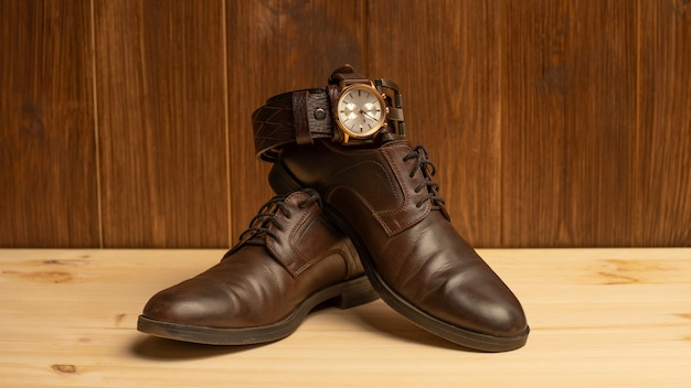 Herenaccessoires met bruine lederen riem, schoenen en horloge op houten achtergrond