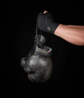 Herenarm gewikkeld in een zwart elastisch sportverband houdt een paar oude vintage lederen bokshandschoenen vast