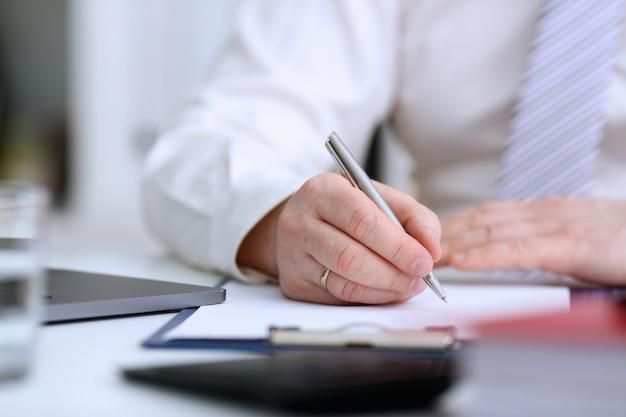 Herenarm in pak en stropdas met zilveren pen