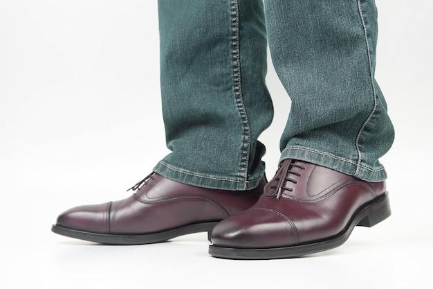 Herenbenen in jeans geschoeid in klassieke bruine oxford schoenen. leer modieuze schoenen voor heren