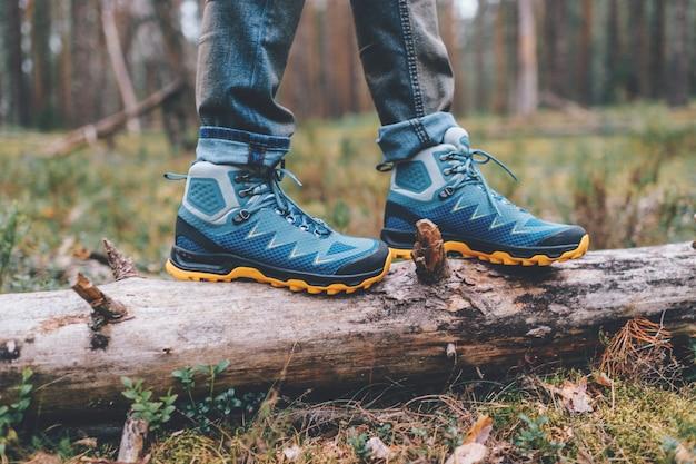 Herenbenen in trekkingschoenen voor buitenactiviteiten.