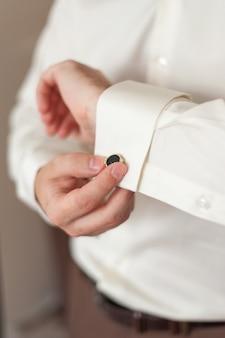 Herenhanden verstellen manchetknopen op de mouwen.