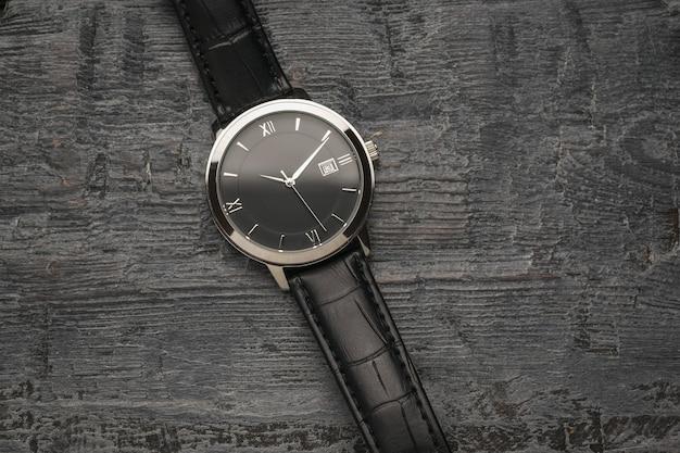 Herenhorloge met handen op een houten ondergrond. een modieus en stijlvol herenaccessoire.