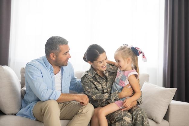 Hereniging thuis. familie voelt zich gelukkig terwijl ze thuis herenigd wordt met een militaire vrouw die naar huis terugkeert