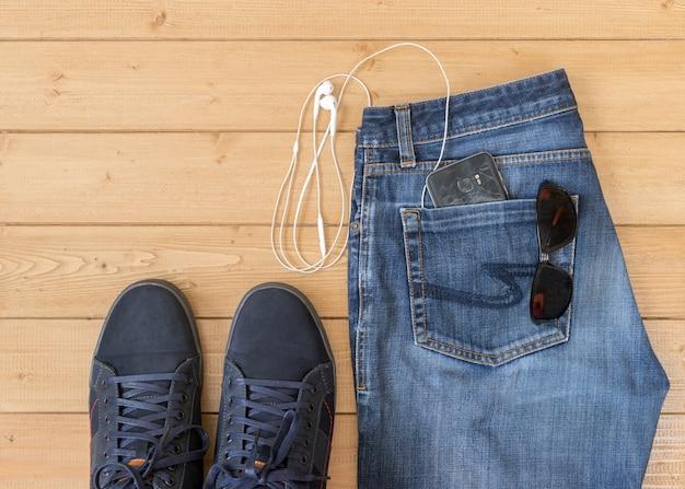 Herenjeans en accessoires op de houten vloer.
