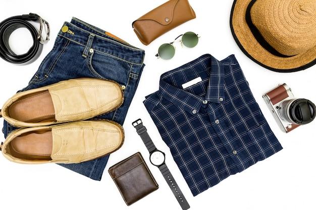 Herenkleding met bruine schoenen, blauw shirt en zonnebril op witte achtergrond.