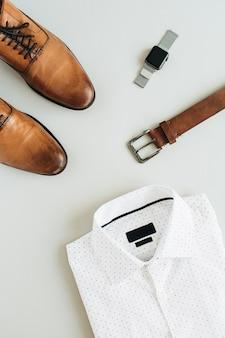 Herenmode-compositie met horloge, overhemd, riem en schoenen