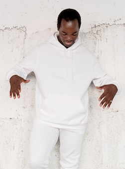 Herenmode hoodie op man met betonnen muur