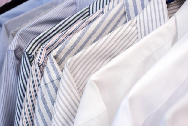Herenoverhemden hangen op een rij in een rij