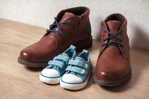 Herenschoenen en kinderschoenen op een houten vlotter