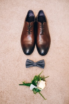Herenschoenen van bruin leer. bruiloft concept. mannen schoenen, vlinderdas en corsages, bovenaanzicht.