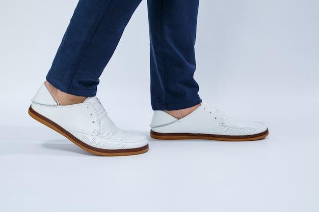 Herenvoeten in witte alledaagse sneakers gemaakt van natuurlijk leer met vetersluiting.