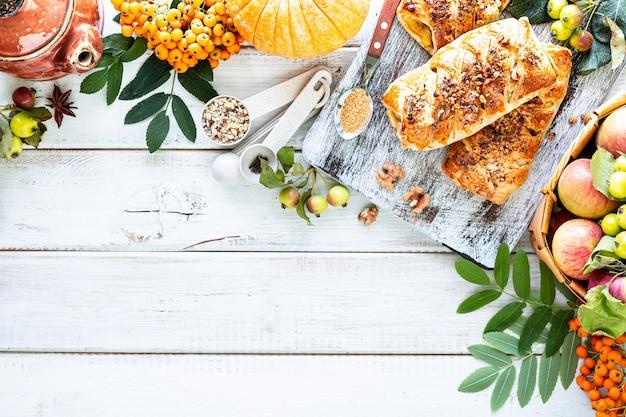Herfst achtergrond ... bakken met pompoen en kaneel op een witte houten achtergrond. bovenaanzicht, rustieke stijl, kopie ruimte