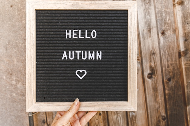 Herfst achtergrond. hand met zwarte letterbord met tekst hallo herfst