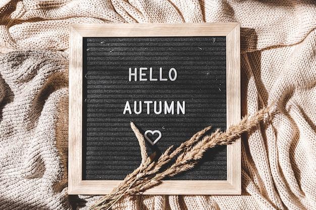 Herfst achtergrond. letterbord met tekst hallo herfst liggend op witte gebreide trui