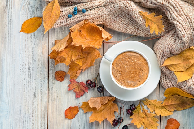Herfst achtergrond met een kopje koffie een trui en gebladerte op een beige achtergrond