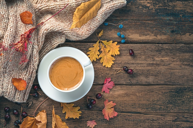Herfst achtergrond met een kopje koffie en droge bladeren op een houten tafel getinte afbeelding