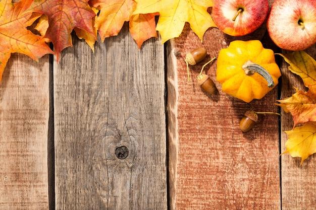 Herfst achtergrond met esdoorn bladeren, pompoen, eikels en appels