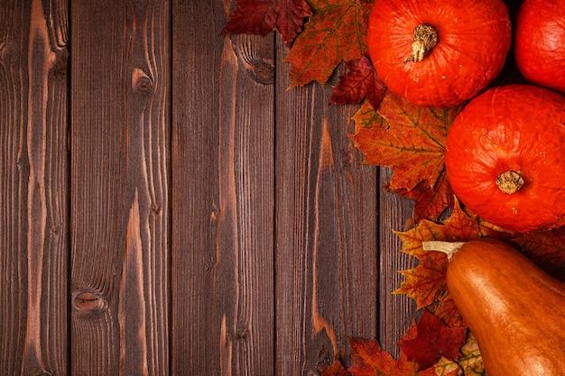 Herfst achtergrond met gekleurde bladeren en pompoenen