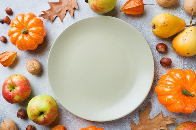 Herfst achtergrond met gele bladeren, pompoenen appels peren en noten