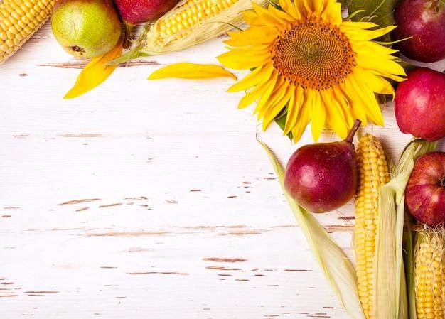 Herfst achtergrond met maïs, zonnebloem en peren. oogst vakantie concept.