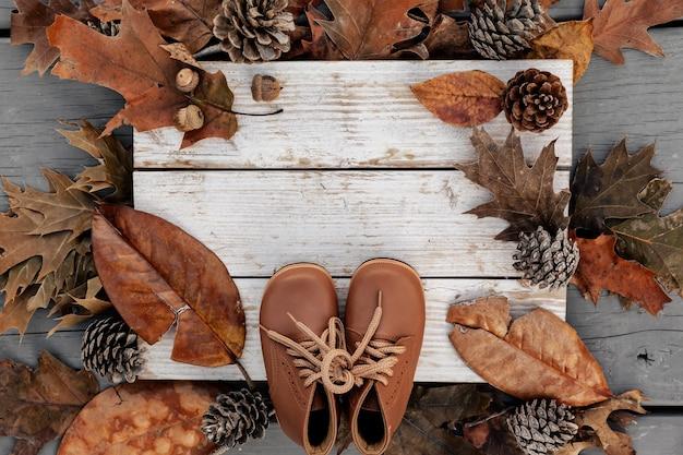 Herfst achtergrond met natuurlijke bladeren, dennenappels en lederen schoenen op oud hout met kopie ruimte, concept van seizoen vakantie