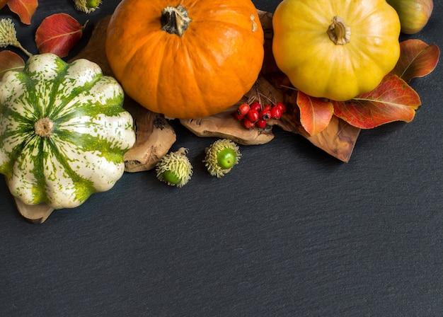 Herfst achtergrond - pompoenen, eikels, bladeren en bessen op donkere tafel