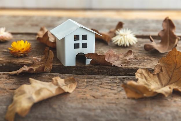 Herfst achtergrond speelgoed huis en gedroogde herfstbladeren op houten achtergrond thanksgiving banner kopie sp...
