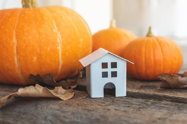 Herfst achtergrond speelgoed huis en pompoen op houten achtergrond thanksgiving banner kopie ruimte hygge ...
