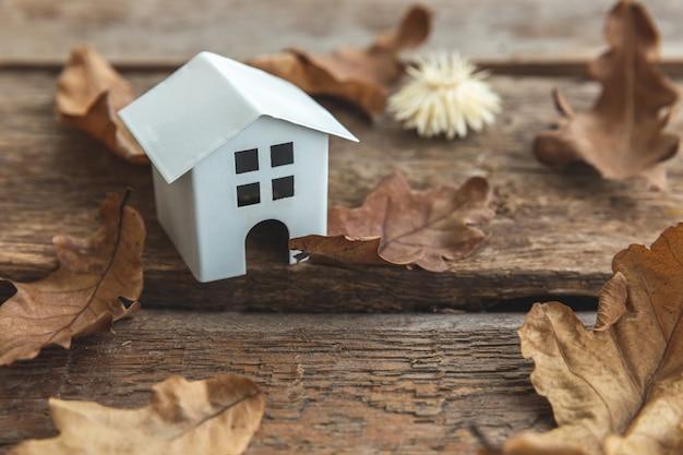 Herfst achtergrond. speelgoedhuis en gedroogde herfstbladeren op houten ondergrond. thanksgiving banner kopie ruimte. hygge stemming koud weer concept. hallo herfst met familie.