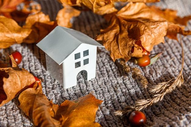 Herfst achtergrond. speelgoedhuis en gedroogde oranje herfst esdoorn bladeren op grijze gebreide trui. thanksgiving banner kopie ruimte. hygge stemming koud weer concept. hallo herfst met familie.