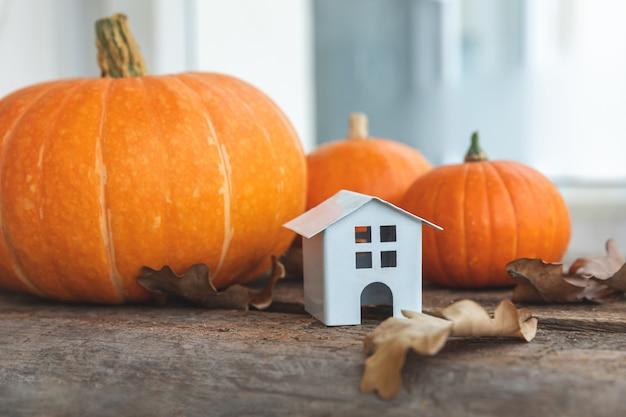 Herfst achtergrond. stuk speelgoed huis en pompoen op houten achtergrond. thanksgiving banner kopie ruimte. hygge stemming, verandering van seizoenen concept. hallo herfst met familie halloween-feest.