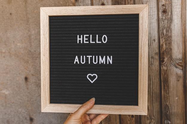 Herfst achtergrond. vrouw hand met zwarte letter bord met tekst zin hallo herfst op houten palnks achtergrond. dankzeggingsbanner. hygge-stemming, koud weerconcept