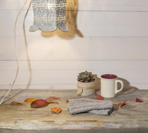 Herfst achtergrond, wollen wanten, kleurrijke bladeren, sappig, kopje koffie op een vintage houten tafel en retro lamp.