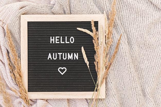 Herfst achtergrond. zwarte letter bord met tekst zin hallo herfst en gedroogd gras liggend op witte gebreide trui. bovenaanzicht, plat gelegd. dankzeggingsbanner. hygge mood koud weer concept