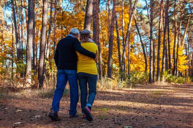 Herfst activiteiten. hoger paar dat in de herfstpark loopt. middelbare leeftijd man en vrouw knuffelen en chillen buitenshuis