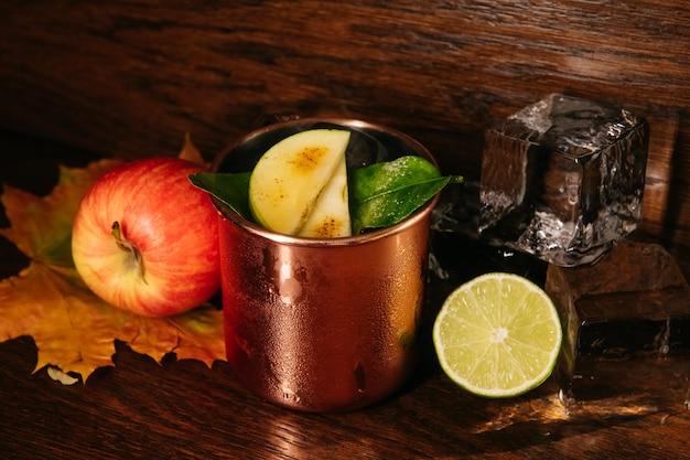 Herfst appelcocktail met ijs en limoen in ijzeren mok op tafel in restaurant