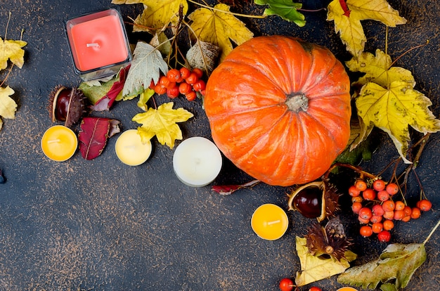 Herfst bladeren, pompoen, kastanjes, kaarsen op een donkere achtergrond