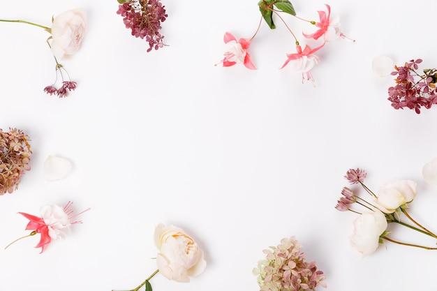 Herfst bloemen samenstelling. frame gemaakt van roze roos, hortensia bloemen op witte grijze achtergrond. plat leggen