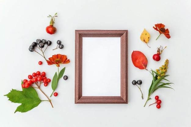 Herfst bloemen samenstelling. verticale frame mockup chokeberry rowan bessen kleurrijke bladeren dogrose bloemen