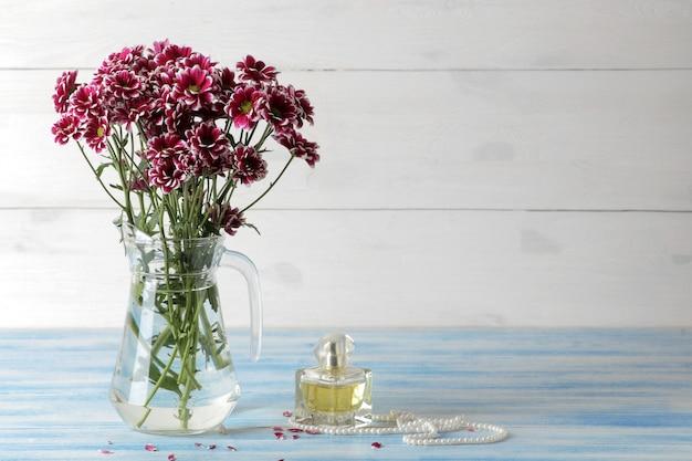 Herfst bloemen van chrysanthemum in een kruik en parfum op een blauwe houten tafel en op wit hout