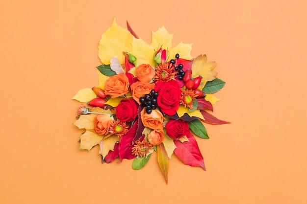 Herfst bloemenboeket herfstbessen, kleurrijke bladeren en rozen op sinaasappel