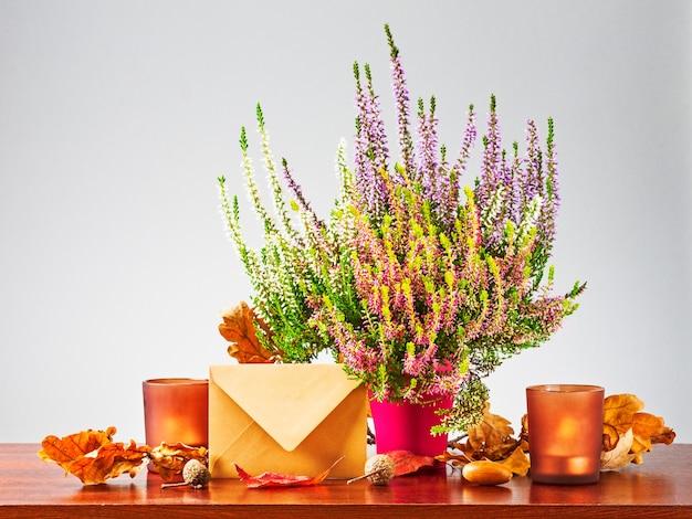 Herfst brief. stilleven met gesloten envelop, heidebloemen, droge eikenbladeren en kaarsen