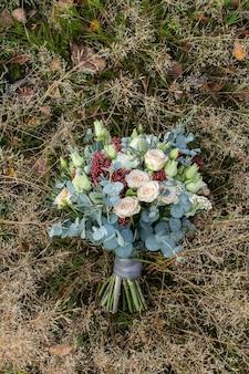 Herfst bruidsboeket: prachtig versierde bruidsbloemsamenstelling ligt op het herfstgras.