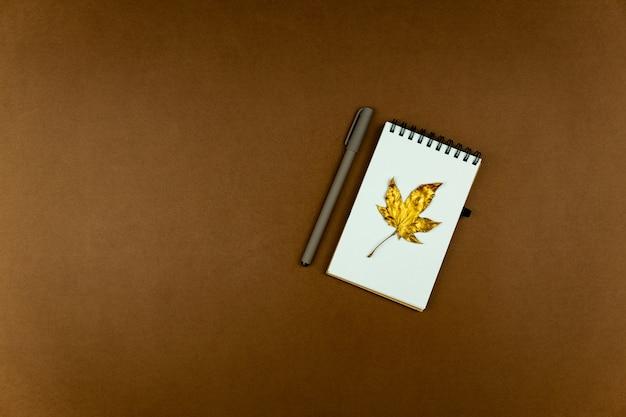 Herfst busines concept - blanco ringgebonden notitieboekje met gouden esdoornblad en pen op bruin, plat leggen