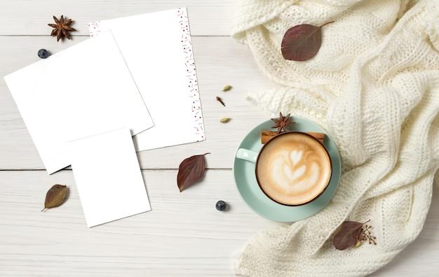 Herfst cappuccino samenstelling. blauwe koffiekopje bovenaanzicht met schuim, kruidnagel, kaneel en warme trui aan witte houten tafel op vel papier. herfst warme dranken concept