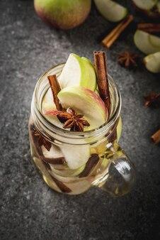 Herfst cocktail. geïnfundeerd dieet ontgift water met appels en kruiden - anijs, kaneel. alcoholcocktail met appelcider. in stenen pot op een zwarte stenen tafel. kopieer ruimte