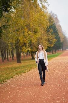 Herfst collectie. aantrekkelijke smilling blonde jonge vrouw, gekleed in basis wit overhemd