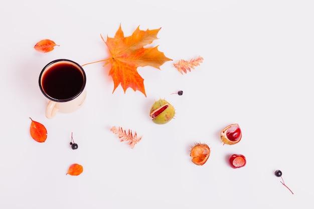 Herfst compositie gemaakt van herfst droge veelkleurige esdoorn bladeren, bessen, kastanje, koffie of thee mok, notitieblok op witte achtergrond. herfst, herfstconcept. platliggend, bovenaanzicht, kopieerruimte